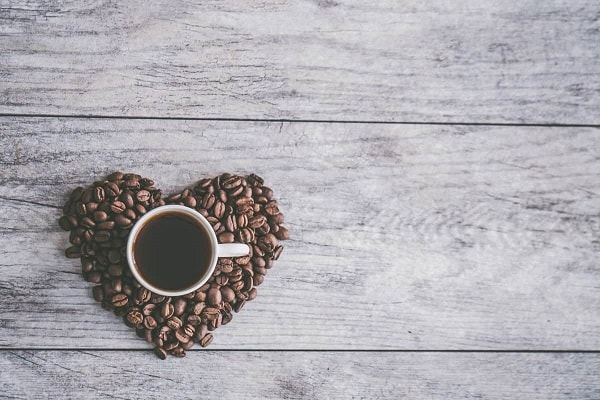 coffee cup full of coffee on heart shaped coffee beans
